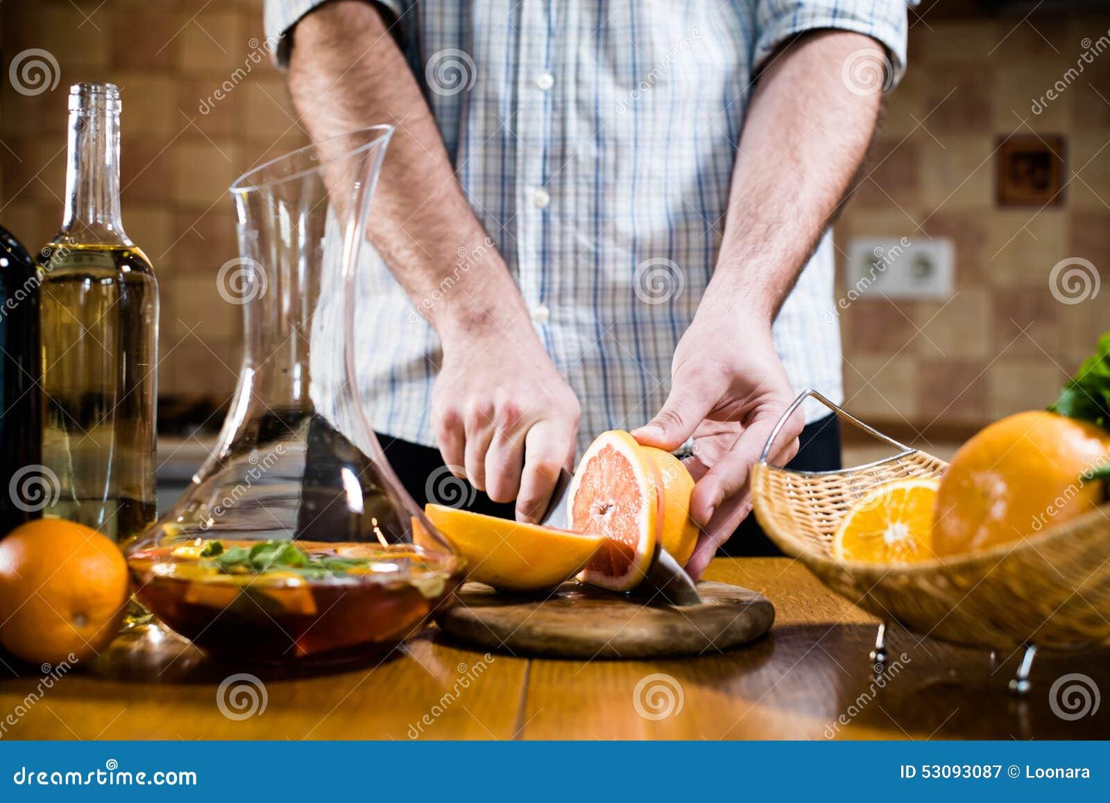El hombre corta los pomelos frescos