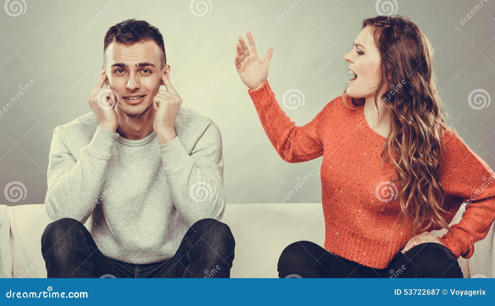 El hombre de griterío de la mujer enojada de la furia se cierra los oídos