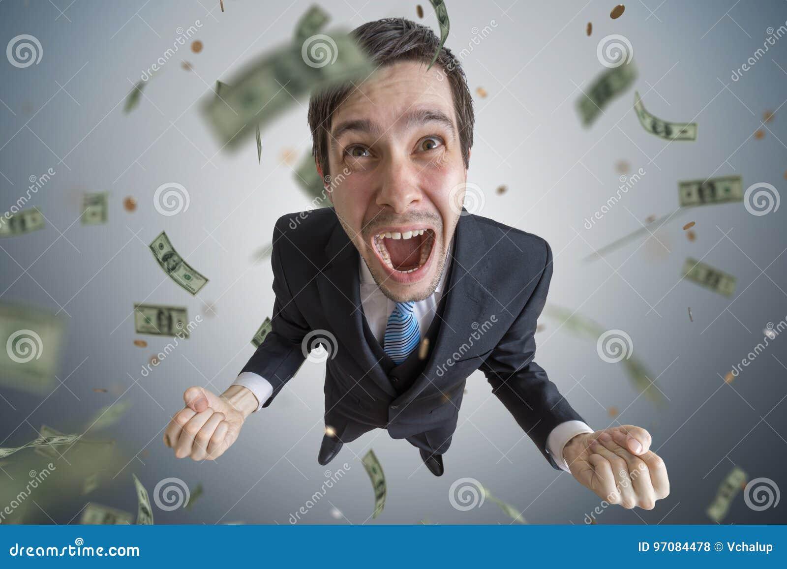 El hombre de negocios acertado joven es un ganador El dinero está cayendo desde arriba