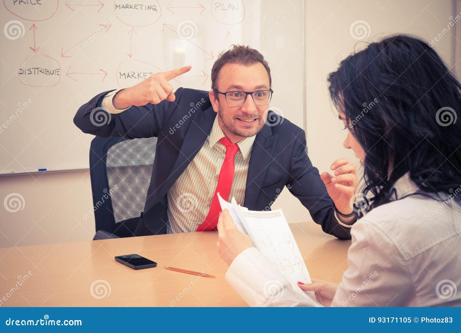 El hombre de negocios amenaza al compañero de trabajo femenino