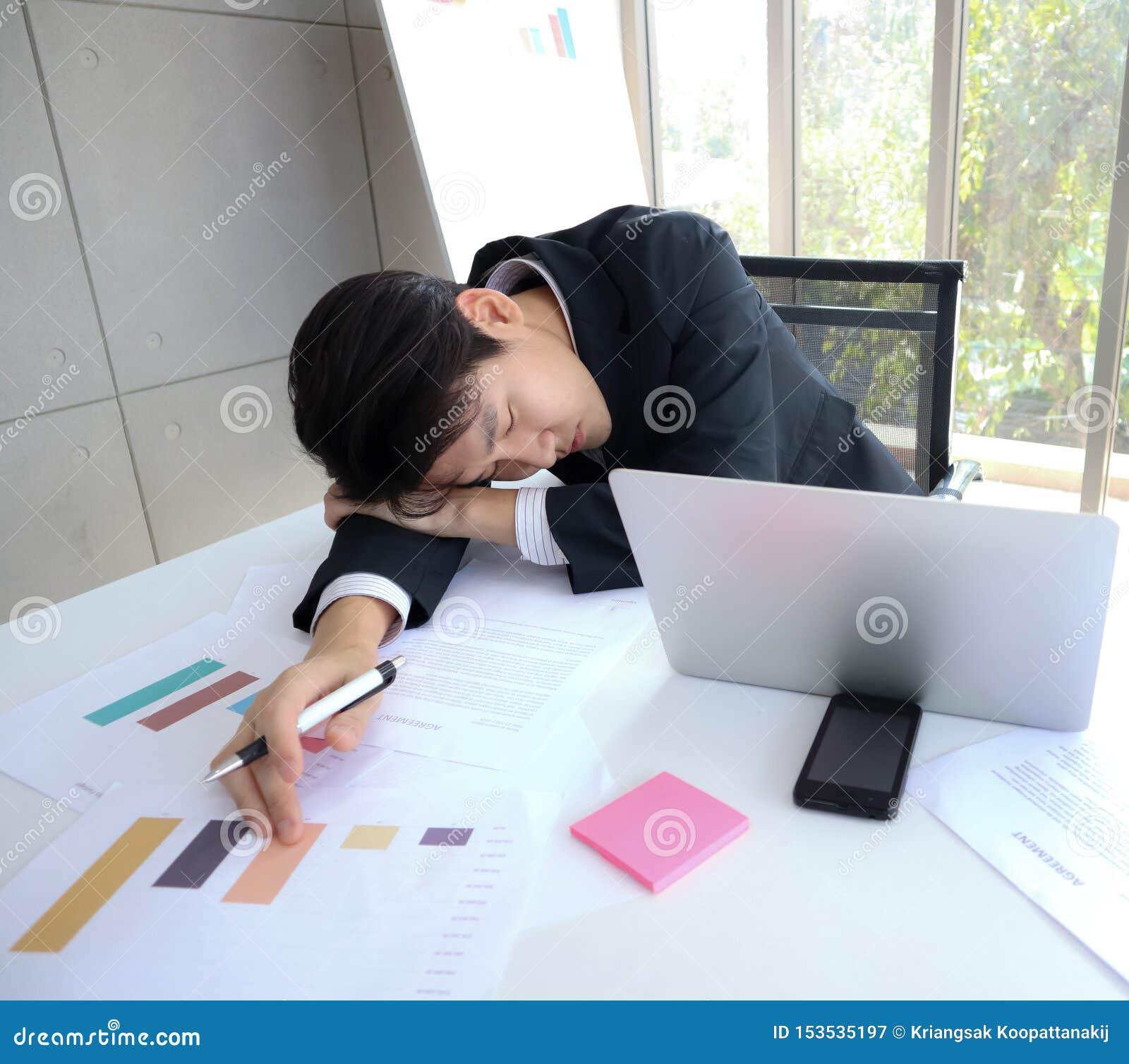 El hombre de negocios asiático hermoso joven se cae dormido en el escritorio de trabajo
