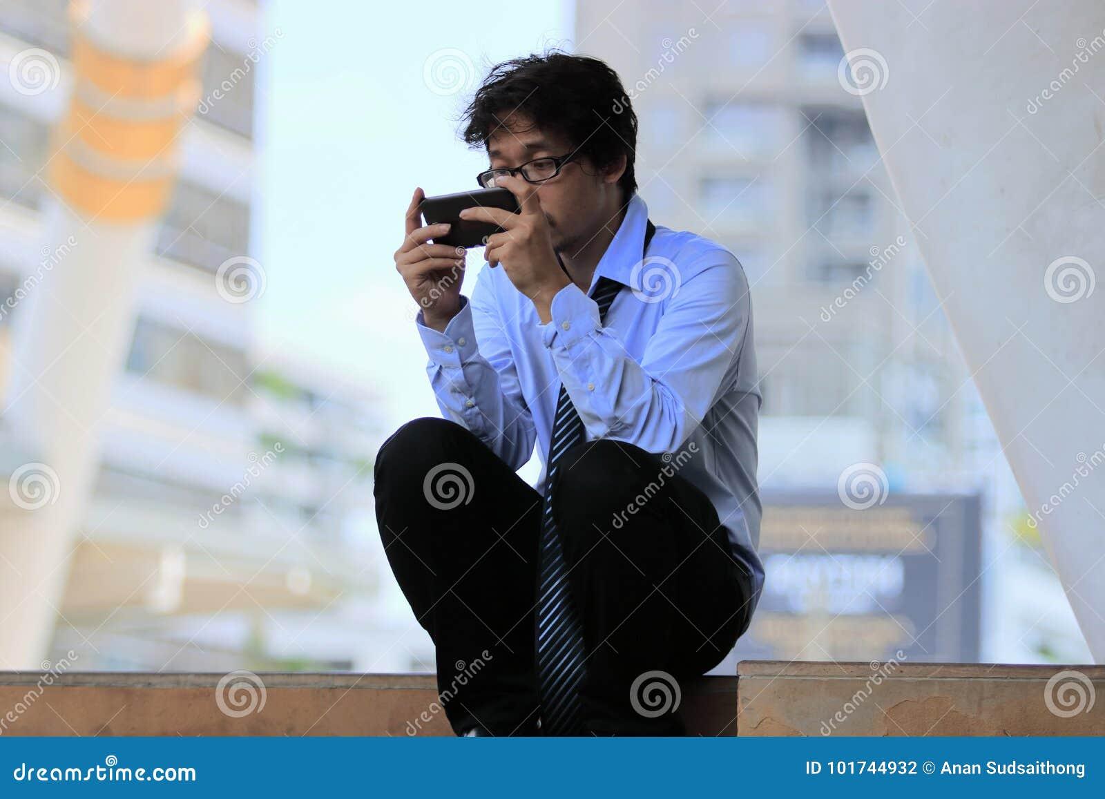 El hombre de negocios asiático joven parado usando el teléfono elegante móvil encuentra un trabajo Concepto deprimido del negocio