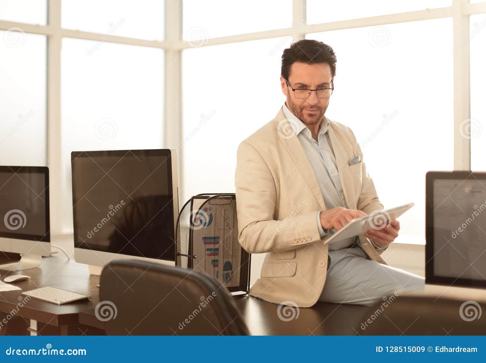 El hombre de negocios atento utiliza una tableta digital en una oficina moderna