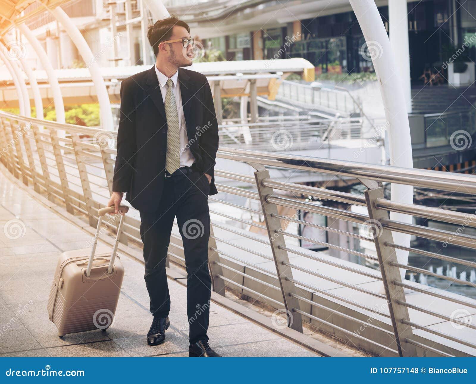 El hombre de negocios con el bolso del viaje está en viaje de negocios