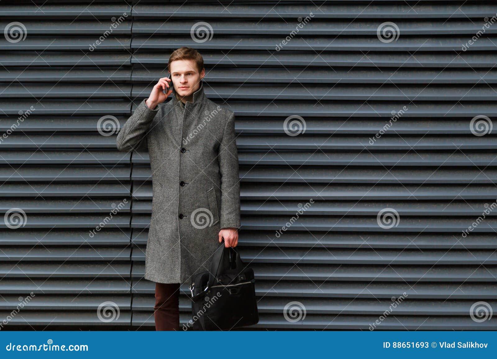 El hombre de negocios confiado joven en una capa y una cartera grises en su mano está hablando en el teléfono móvil contra la par