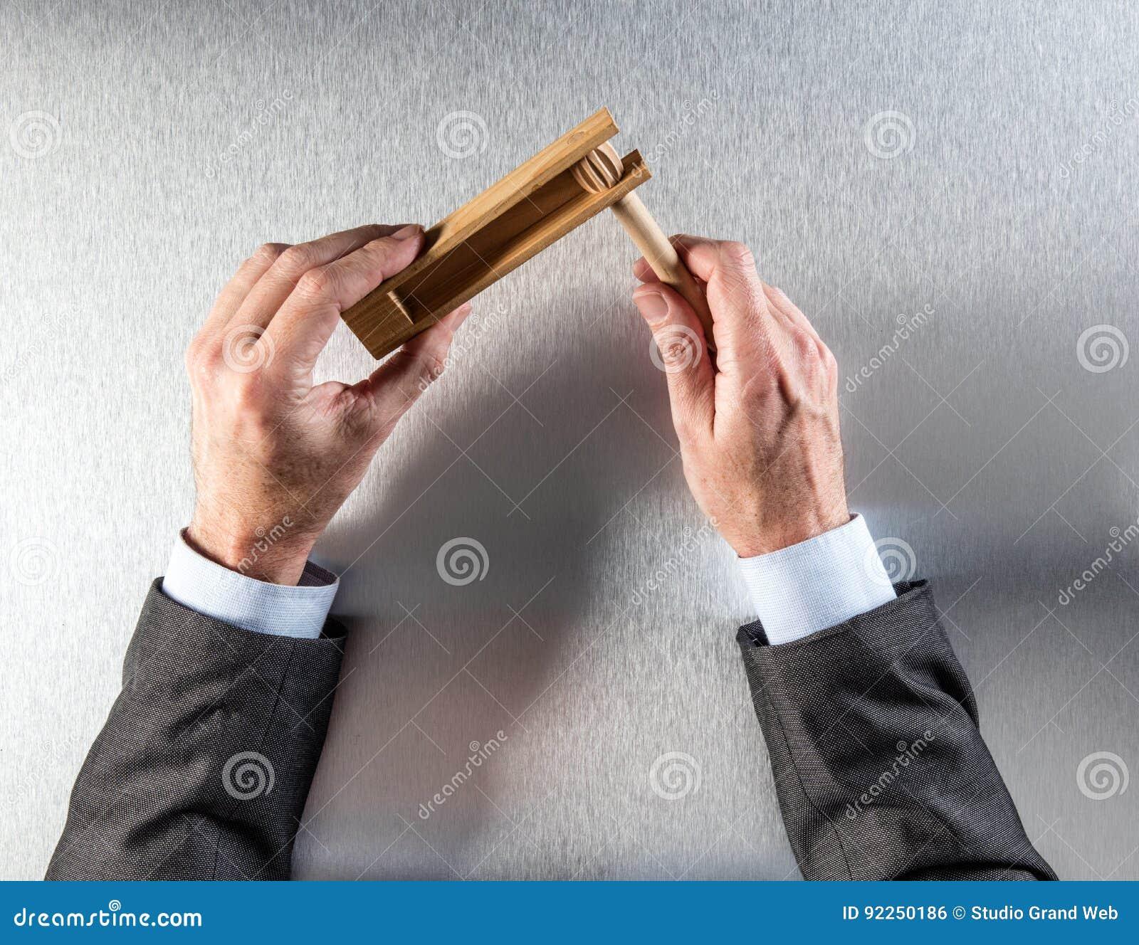 El hombre de negocios da llevar a cabo el traqueteo de madera para la llamada de activación de la oficina