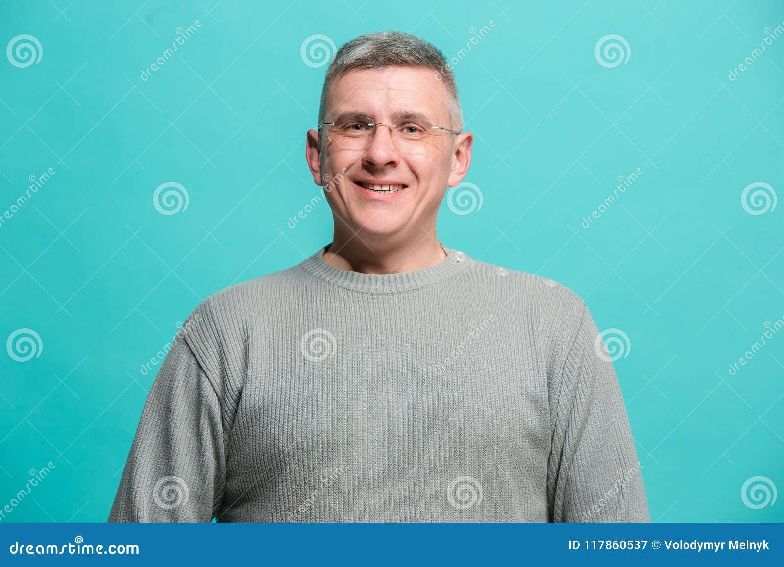 El hombre de negocios feliz que se opone y que sonríe contra fondo azul