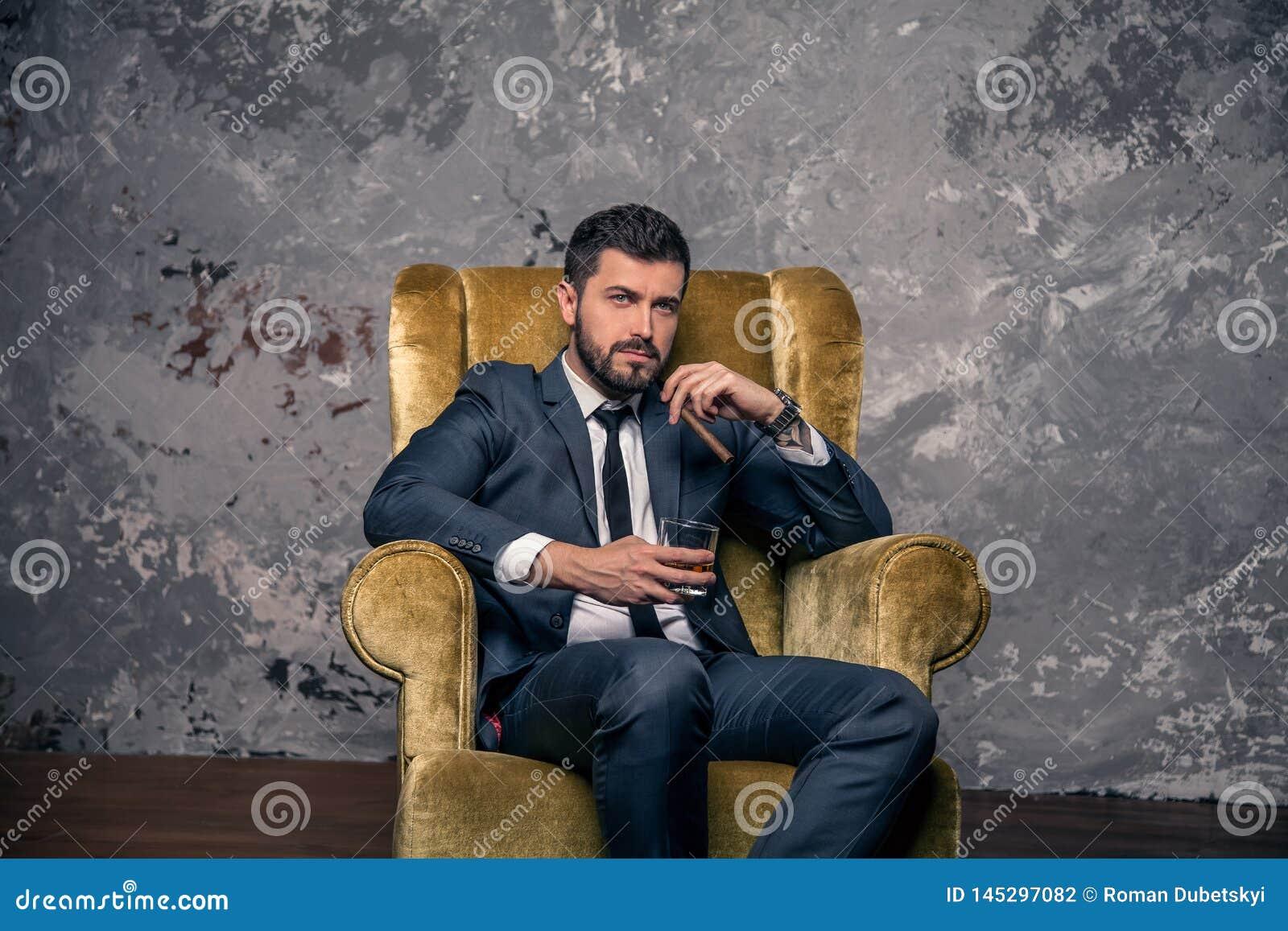 El hombre de negocios hermoso apuesto está tomando un resto que se sienta en la silla y el whisky de consumición con un cigarro