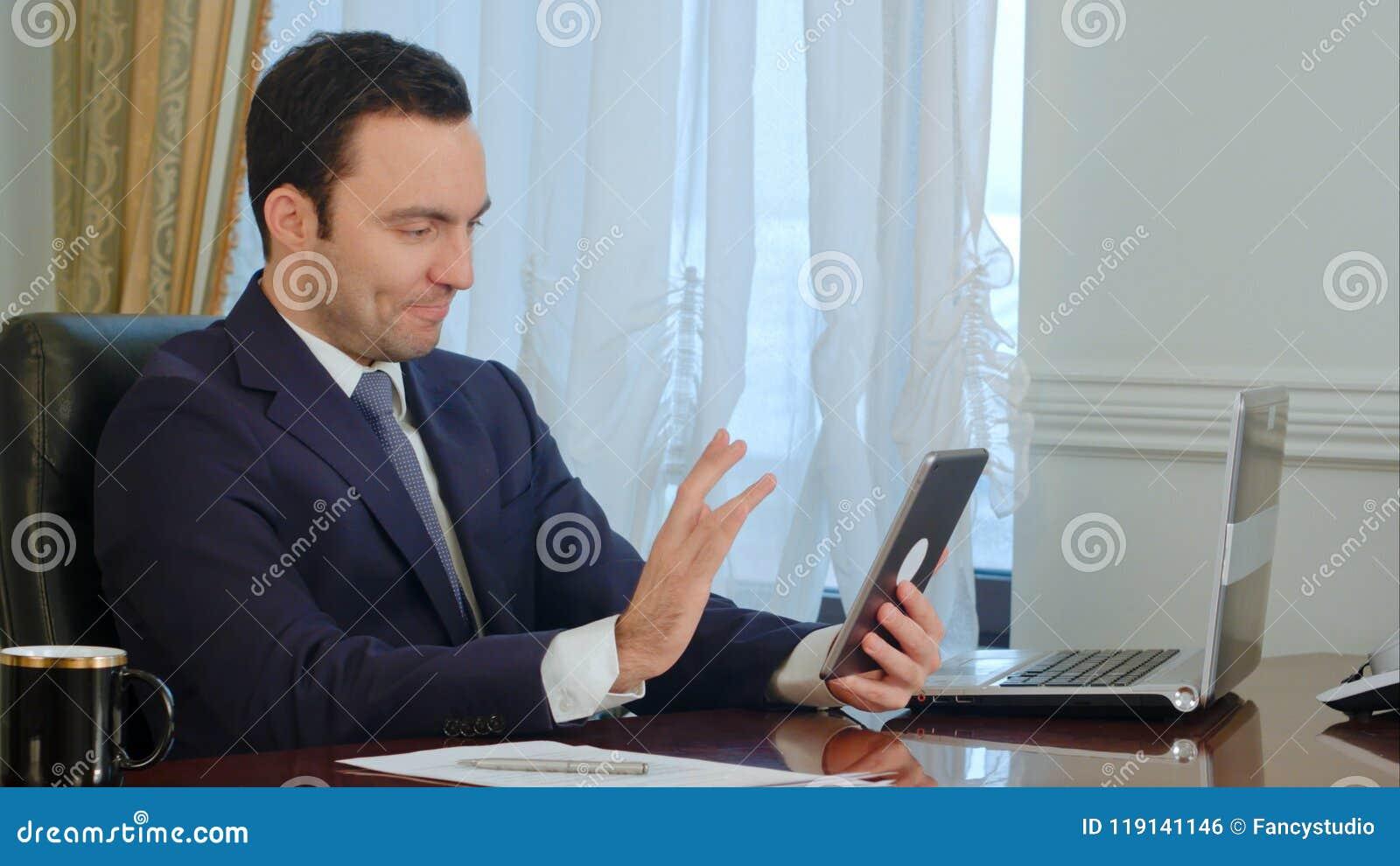 El hombre de negocios hermoso tiene reunión sobre la tableta con los documentos en el escritorio en oficina