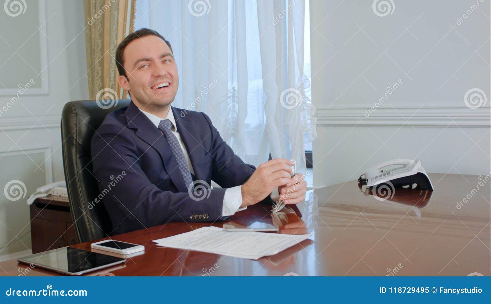 El hombre de negocios joven acertado cuenta el dinero, pareciendo feliz