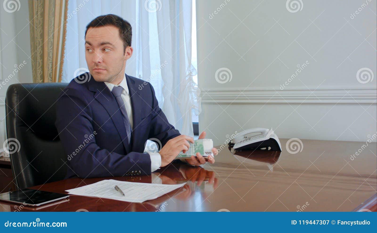 El hombre de negocios joven acertado cuenta las cuentas euro que hablan con el colega en la oficina