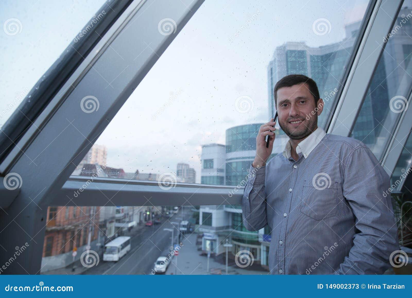 El hombre de negocios joven con una sonrisa en su cara está hablando en su teléfono móvil contra la perspectiva de una ventana pa