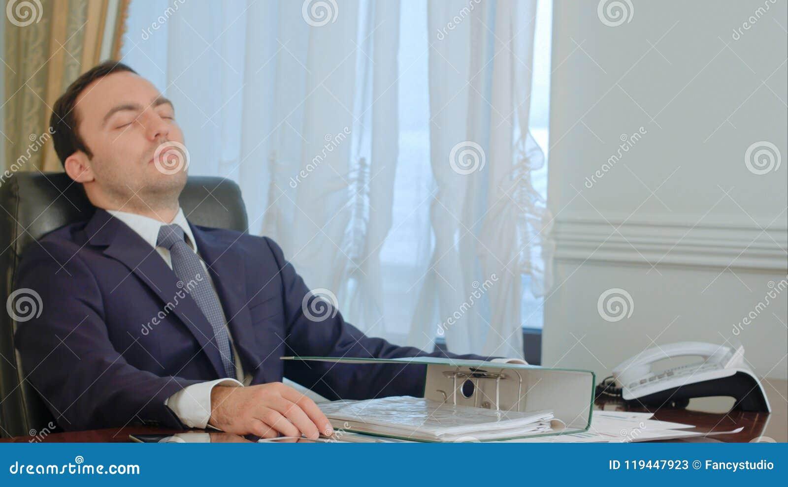 El hombre de negocios joven durmiente despertó por llamada de teléfono en oficina