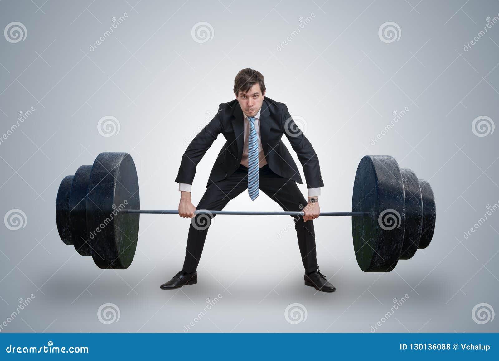 El hombre de negocios joven en traje está levantando pesos pesados