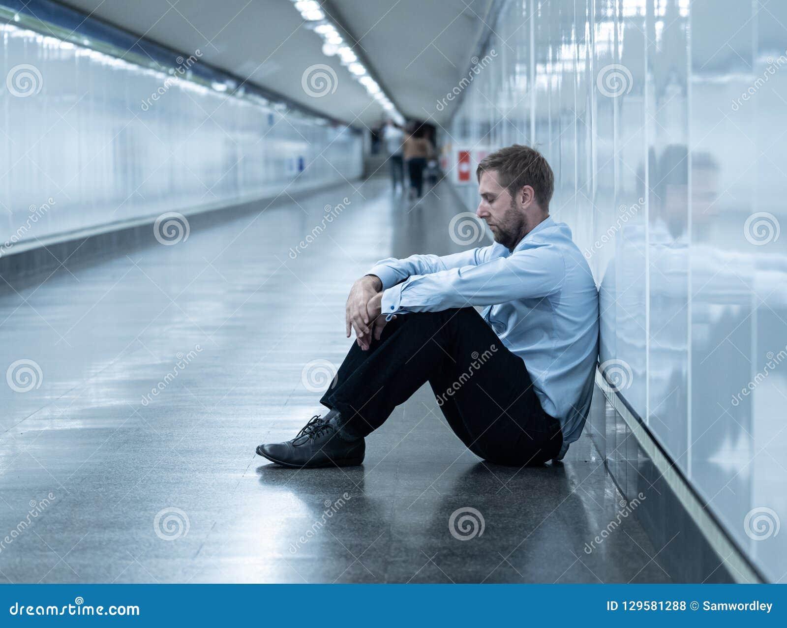 El hombre de negocios joven que el griterío abandonó perdió en la depresión que se sentaba en el subterráneo de tierra