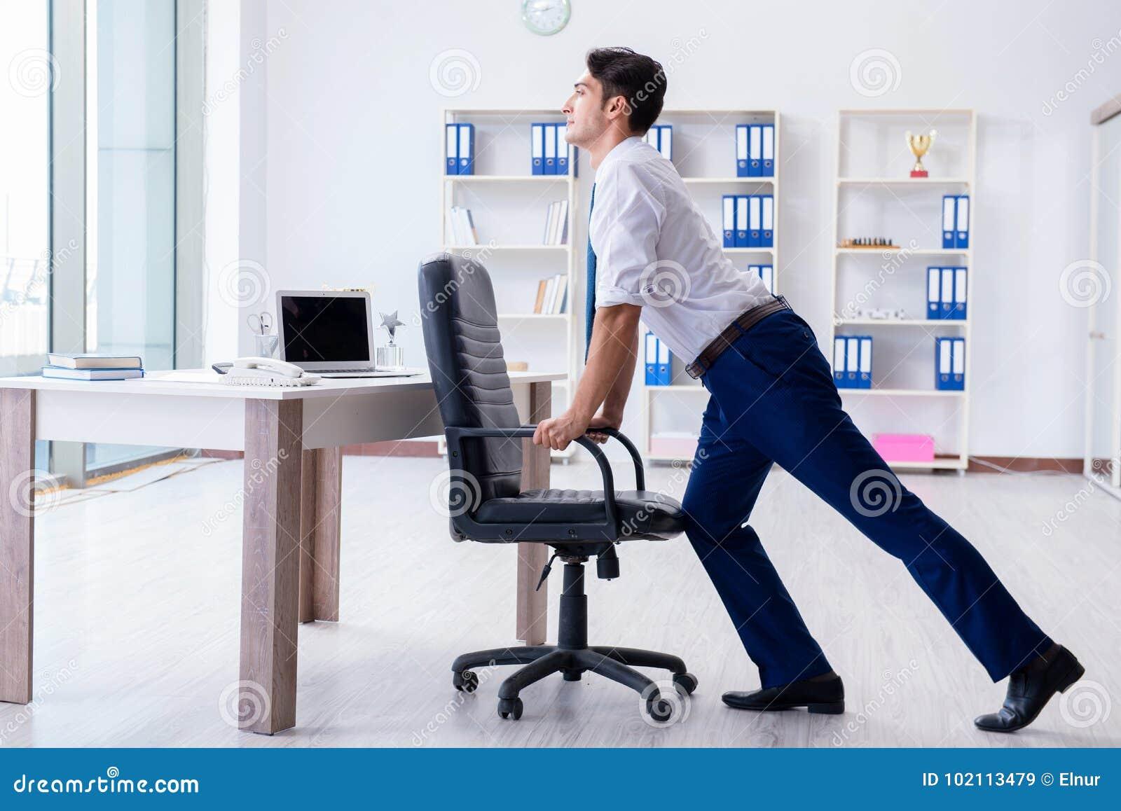 El hombre de negocios joven que hace los deportes que estiran en el lugar de trabajo