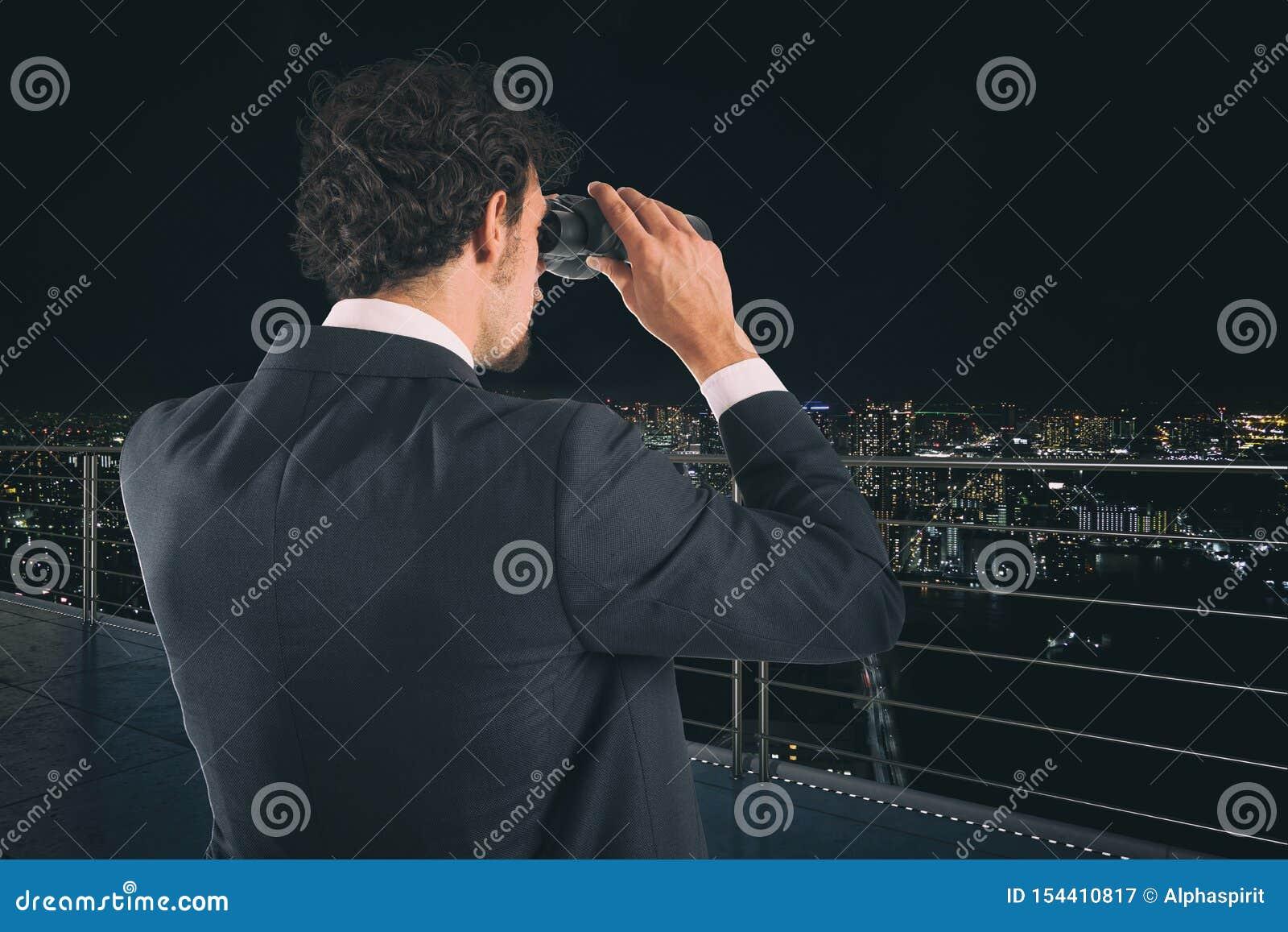 El hombre de negocios mira la ciudad con los prismáticos durante noche Concepto futuro y nuevo de la oportunidad de negocio