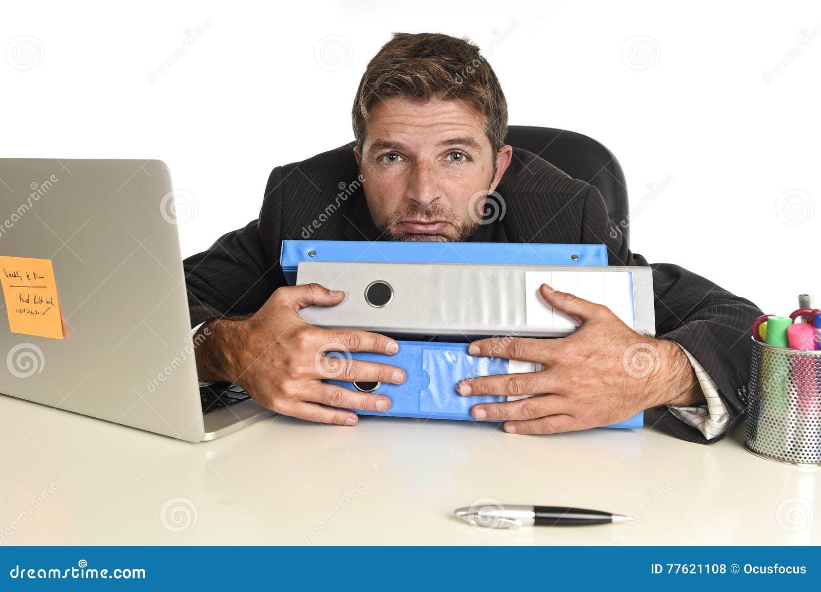 El hombre de negocios perdido cansado que trabajaba en la tensión en el ordenador portátil de la oficina agotó abrumado