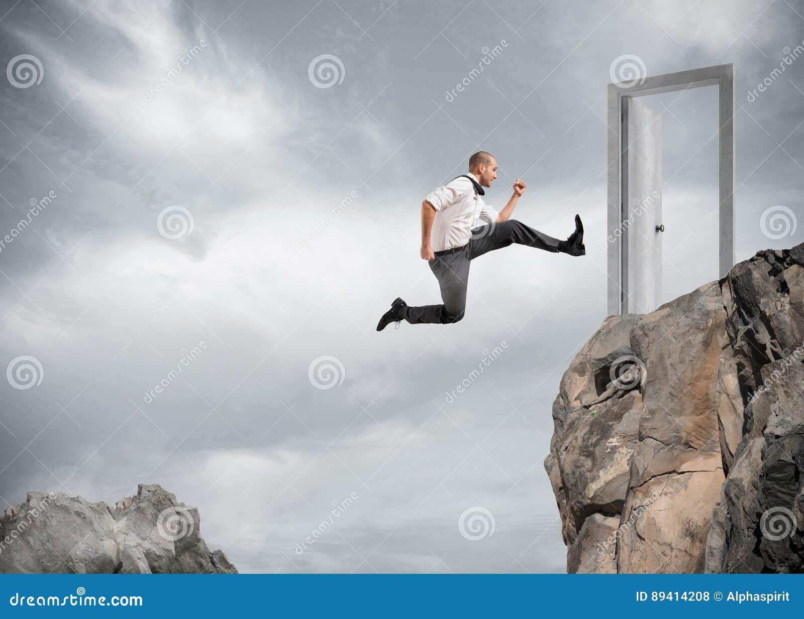 El hombre de negocios que salta sobre las montañas para alcanzar una puerta