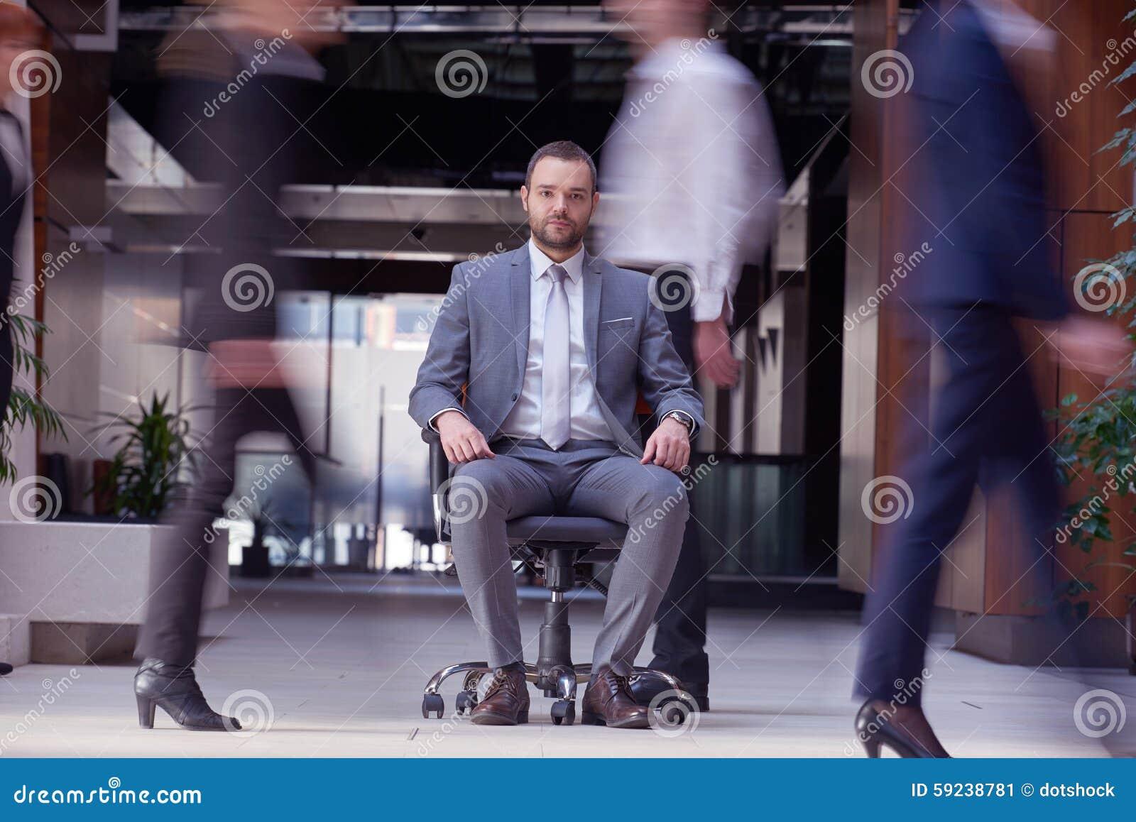 Download El Hombre De Negocios Que Se Sienta En Silla De La Oficina, Gente Agrupa El Paso Cerca Imagen de archivo - Imagen de feliz, relaje: 59238781