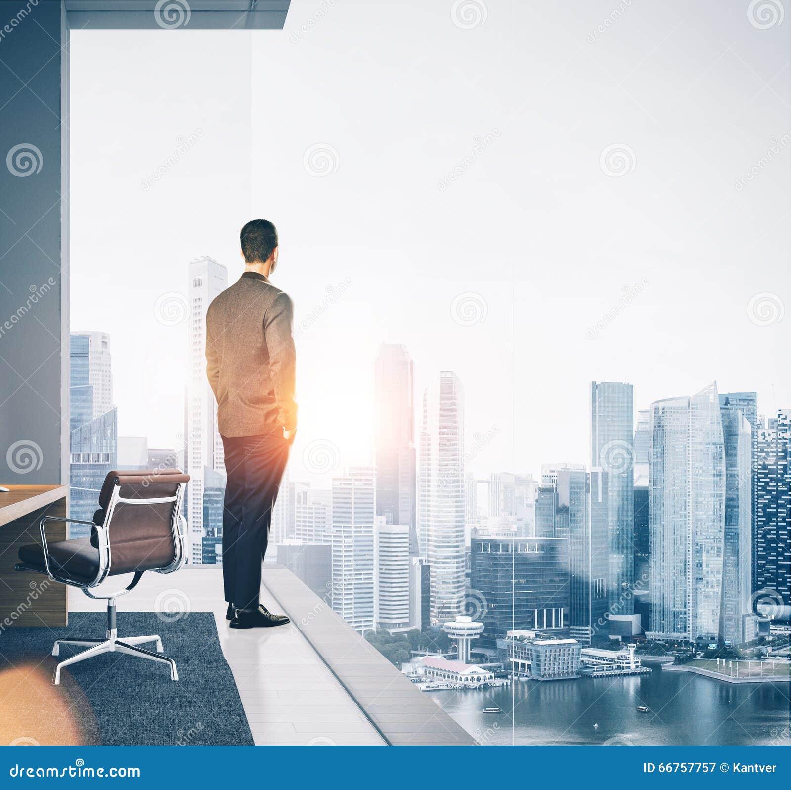 El hombre de negocios se coloca en oficina contemporánea y la mirada de la ciudad cuadrado