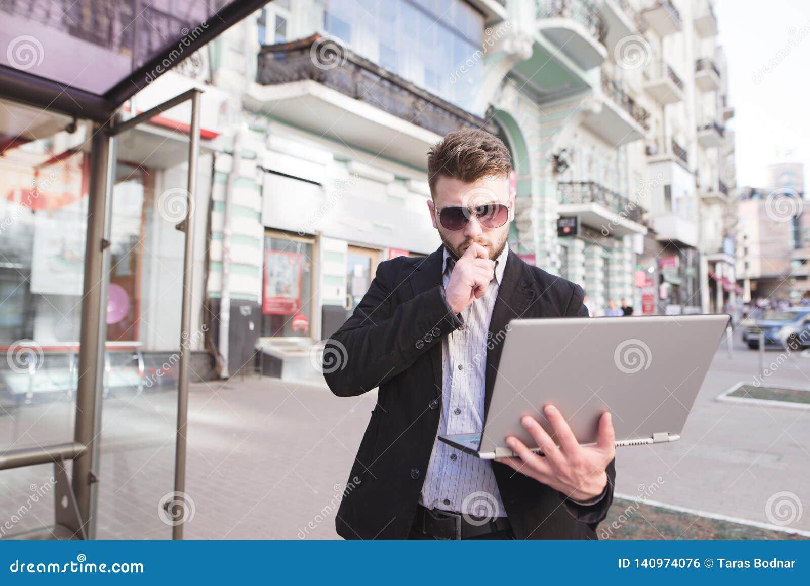 El hombre de negocios se está colocando afuera y está mirando un ordenador portátil Trabajo sobre el ordenador en el aire abierto
