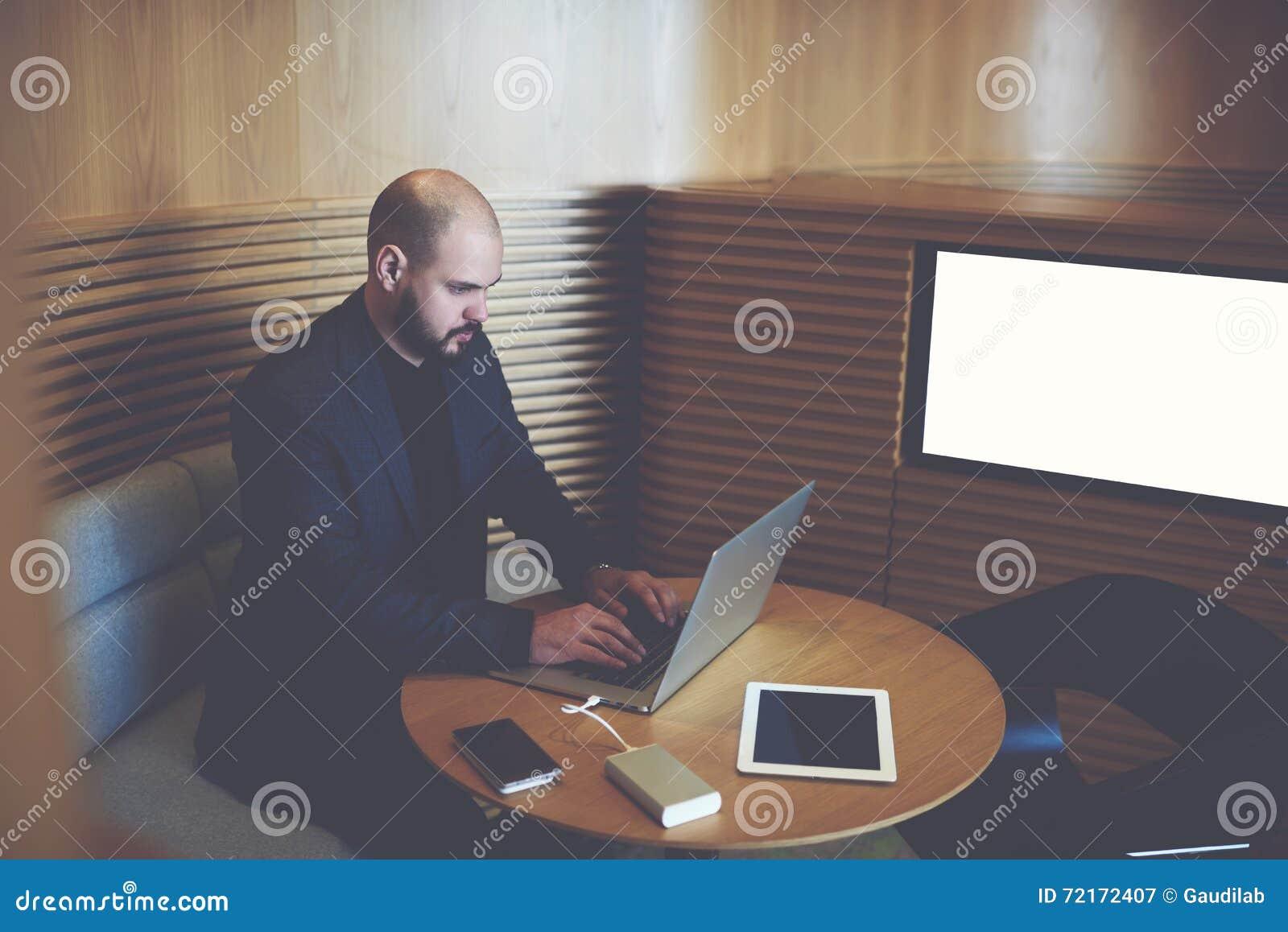 El hombre de negocios se está sentando en pantalla cercana interior de la oficina con mofa encima del espacio de la copia