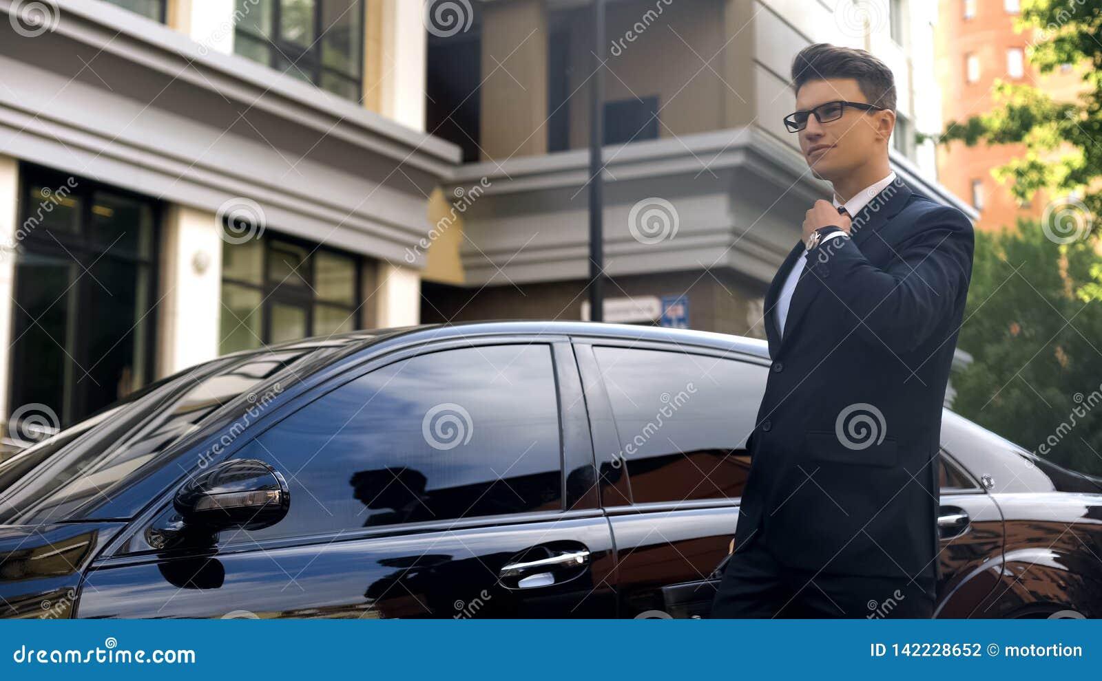 El hombre de negocios seguro de sí mismo que endereza el lazo, yendo a trabajar, alista a los desafíos
