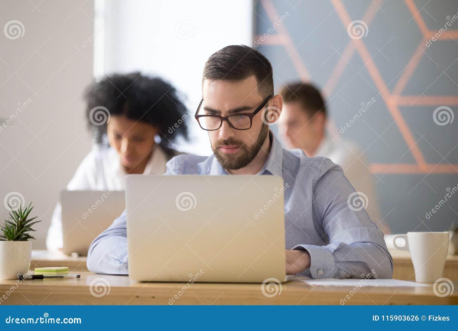 El hombre de negocios serio se centró en trabajo en línea del ordenador en coworking