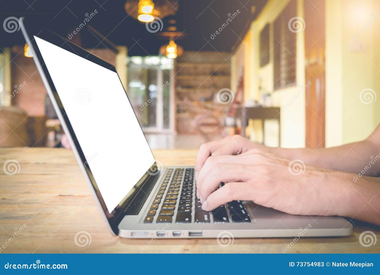 El hombre de negocios utiliza el ordenador portátil en la tabla de madera