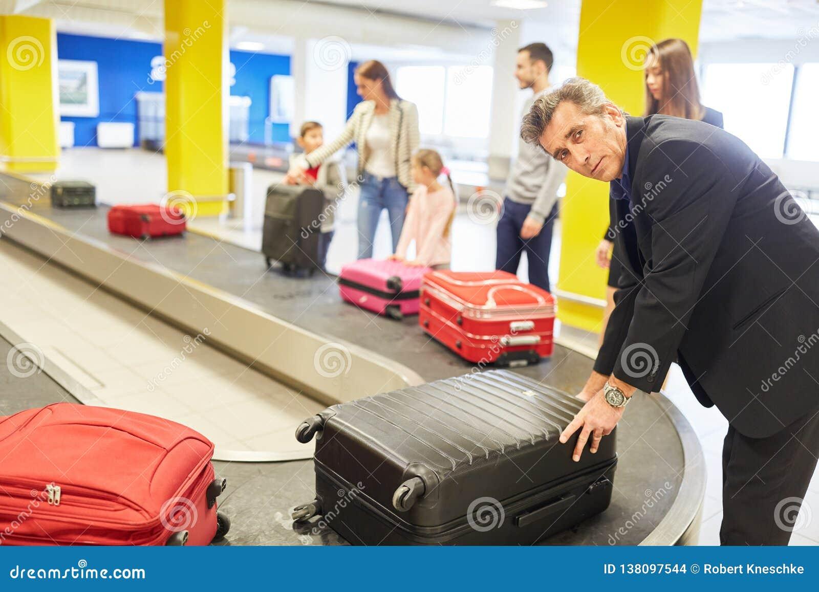 El hombre de negocios y otros pasajeros traen su equipaje