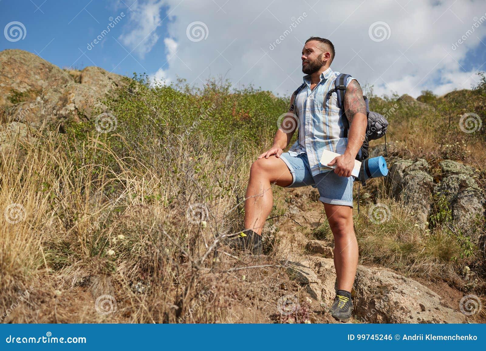 El hombre del viajero con la mochila aumentó las montañas ajardina en fondo Concepto de forma de vida activa