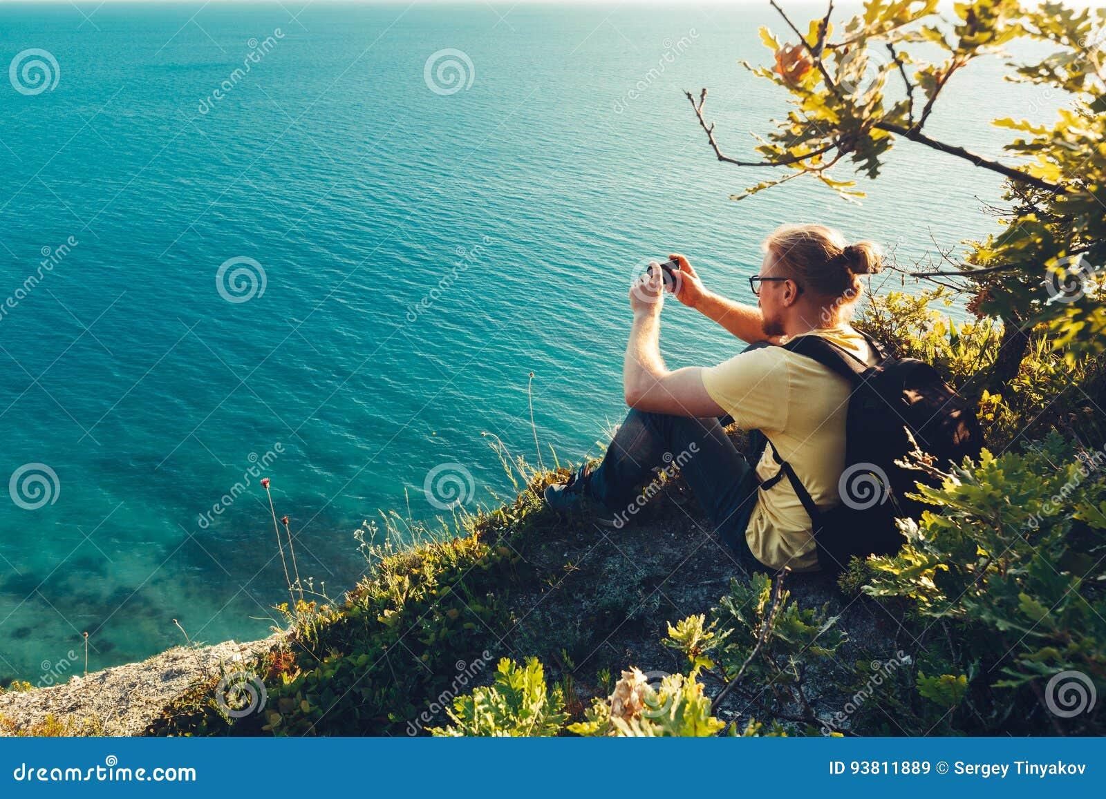 El hombre del viajero se sienta en orilla y toma imágenes del mar en cámara del teléfono celular durante puesta del sol