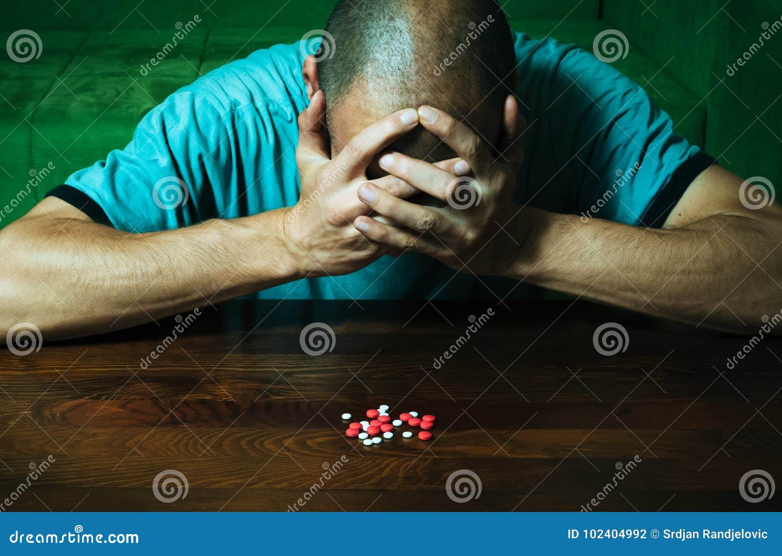 El hombre deprimido que sufre de la depresión suicida quiere confiar suicidio tomando las drogas y las píldoras fuertes del medic