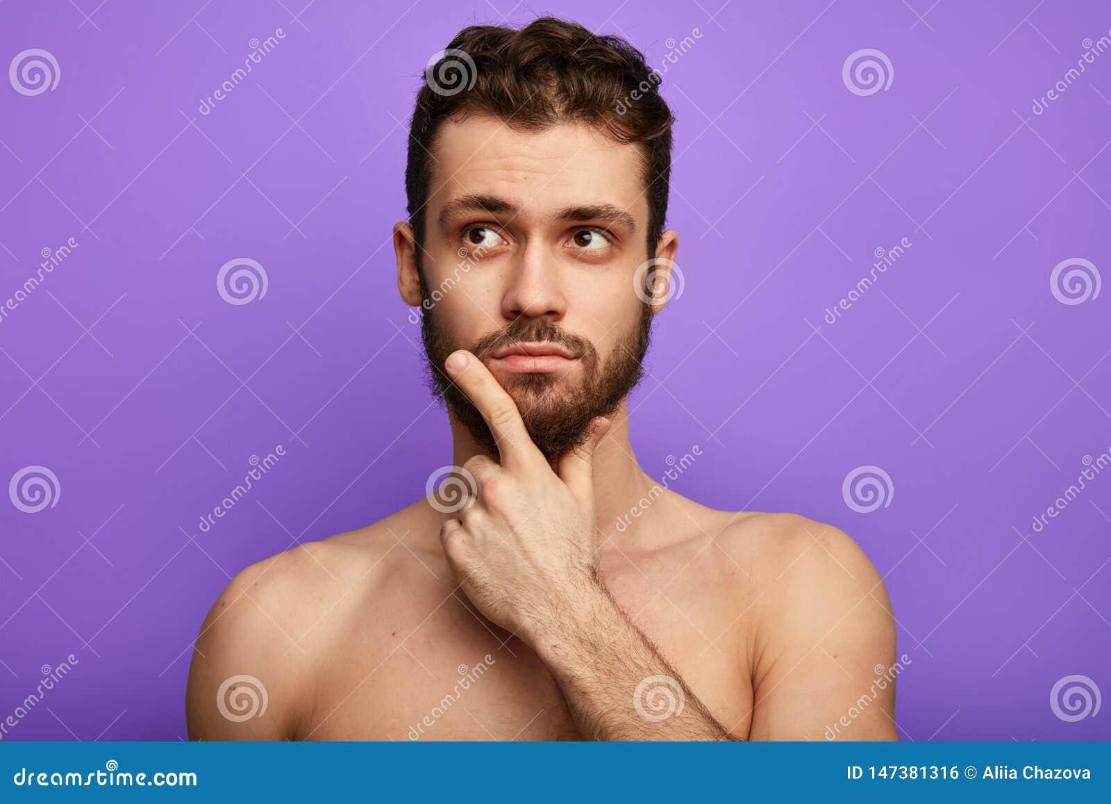 El hombre descamisado muscular es inseguro, sosteniendo la barbilla con el finger