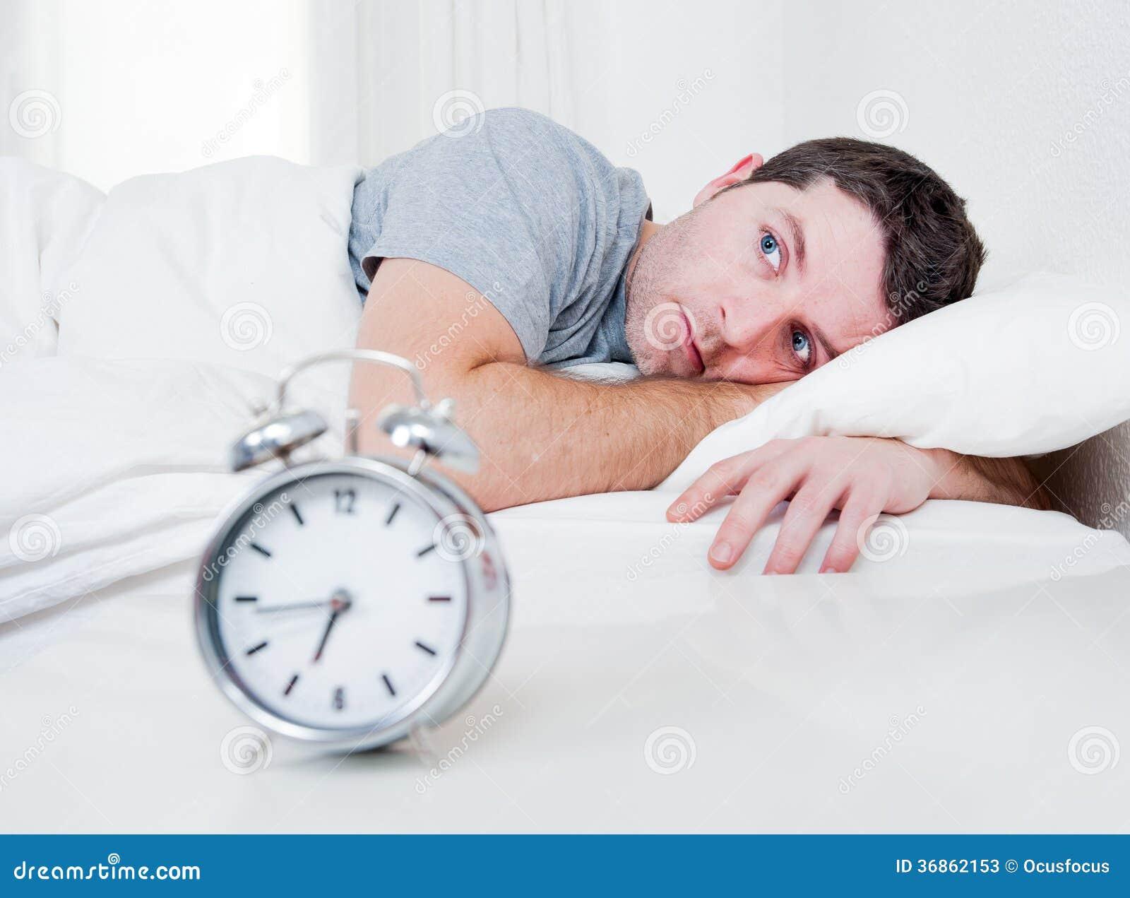 El hombre en cama con los ojos abrió insomnio sufridor y
