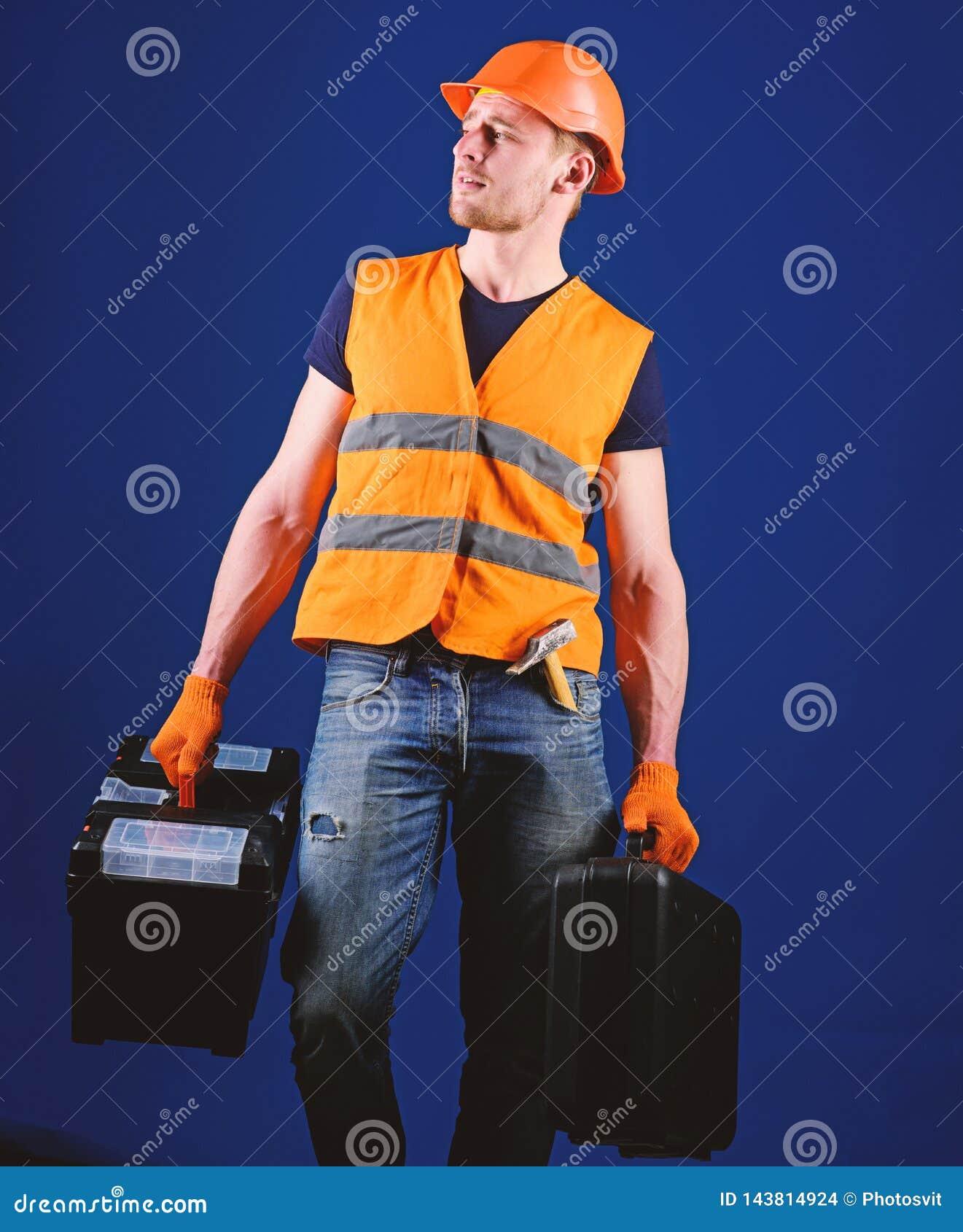 El hombre en el casco, casco sostiene la caja de herramientas y la maleta con las herramientas, fondo azul La manitas, reparador