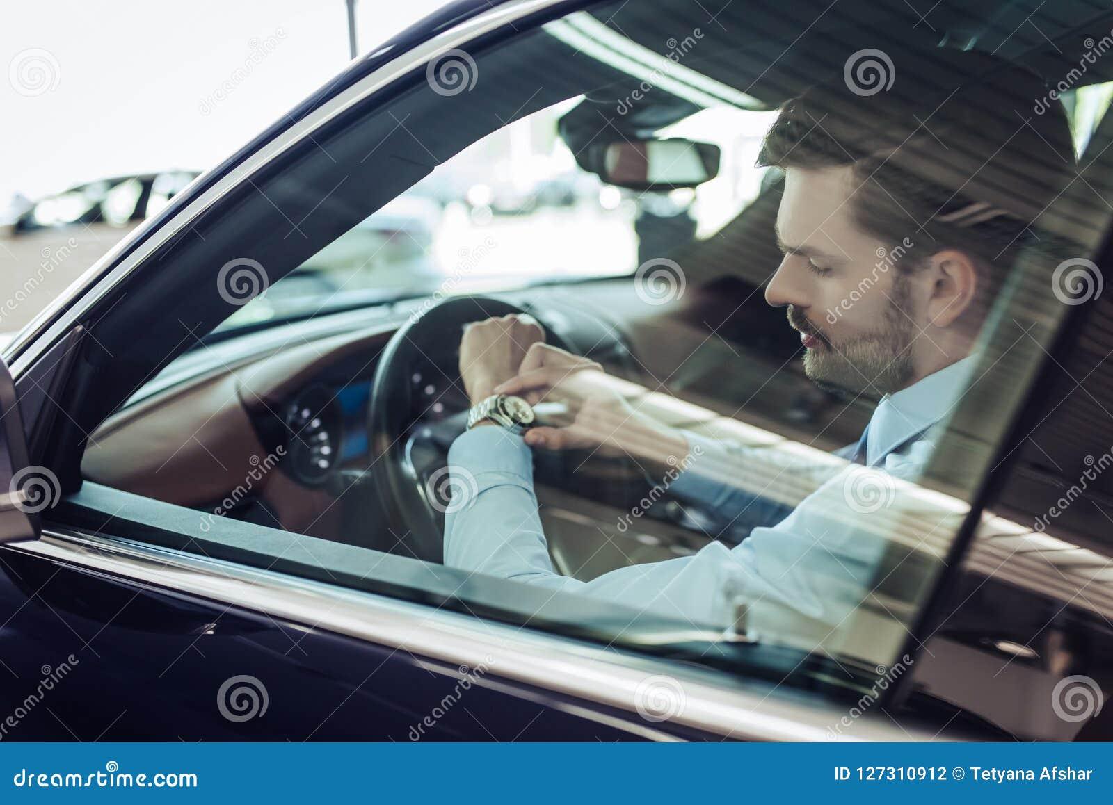 El hombre en el coche mira el reloj