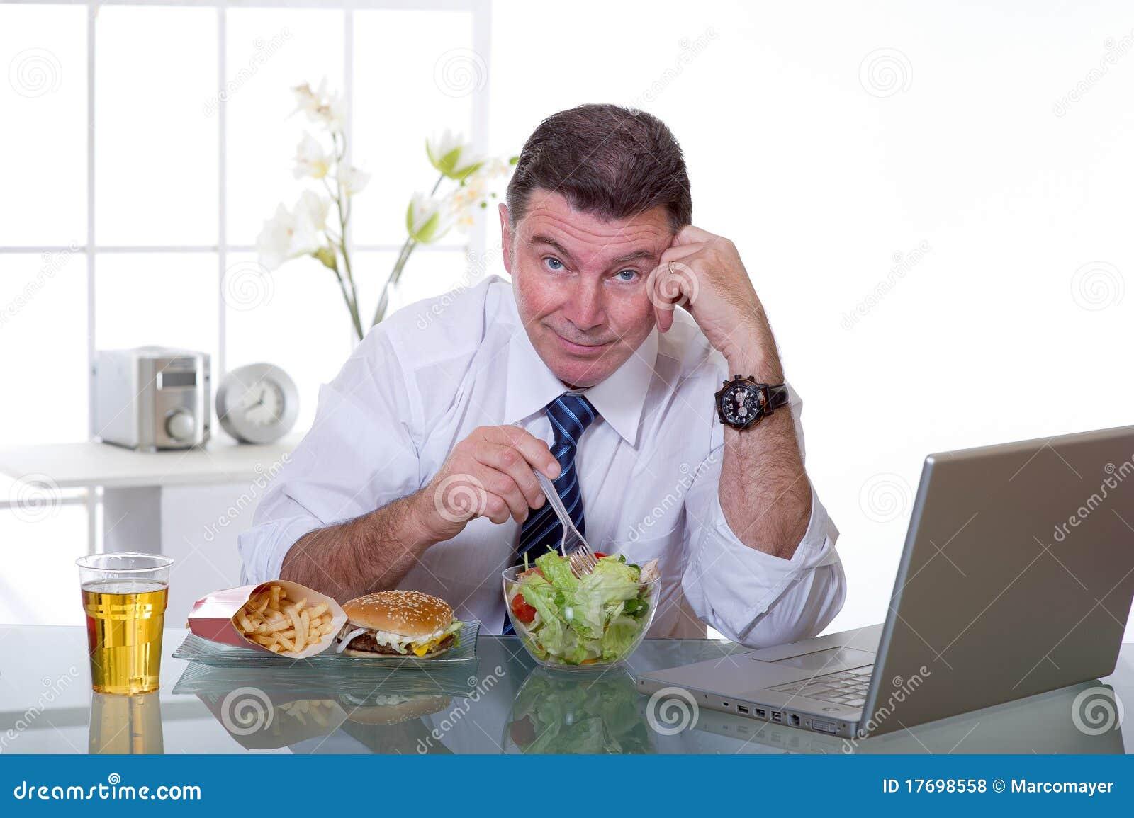 El hombre en la oficina come la ensalada verde