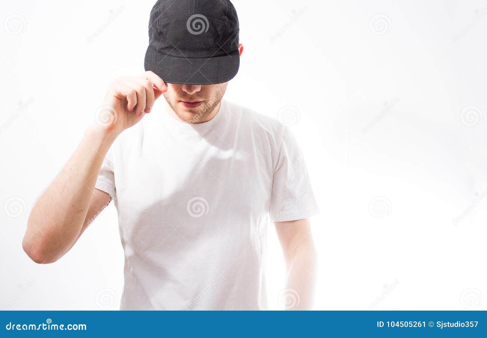 El hombre, en el negro en blanco, gorra de béisbol, snapback en un fondo blanco, mofa para arriba, espacio libre, presentación de