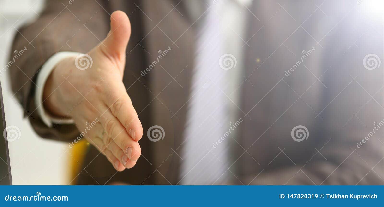 El hombre en traje y el lazo dan la mano como hola