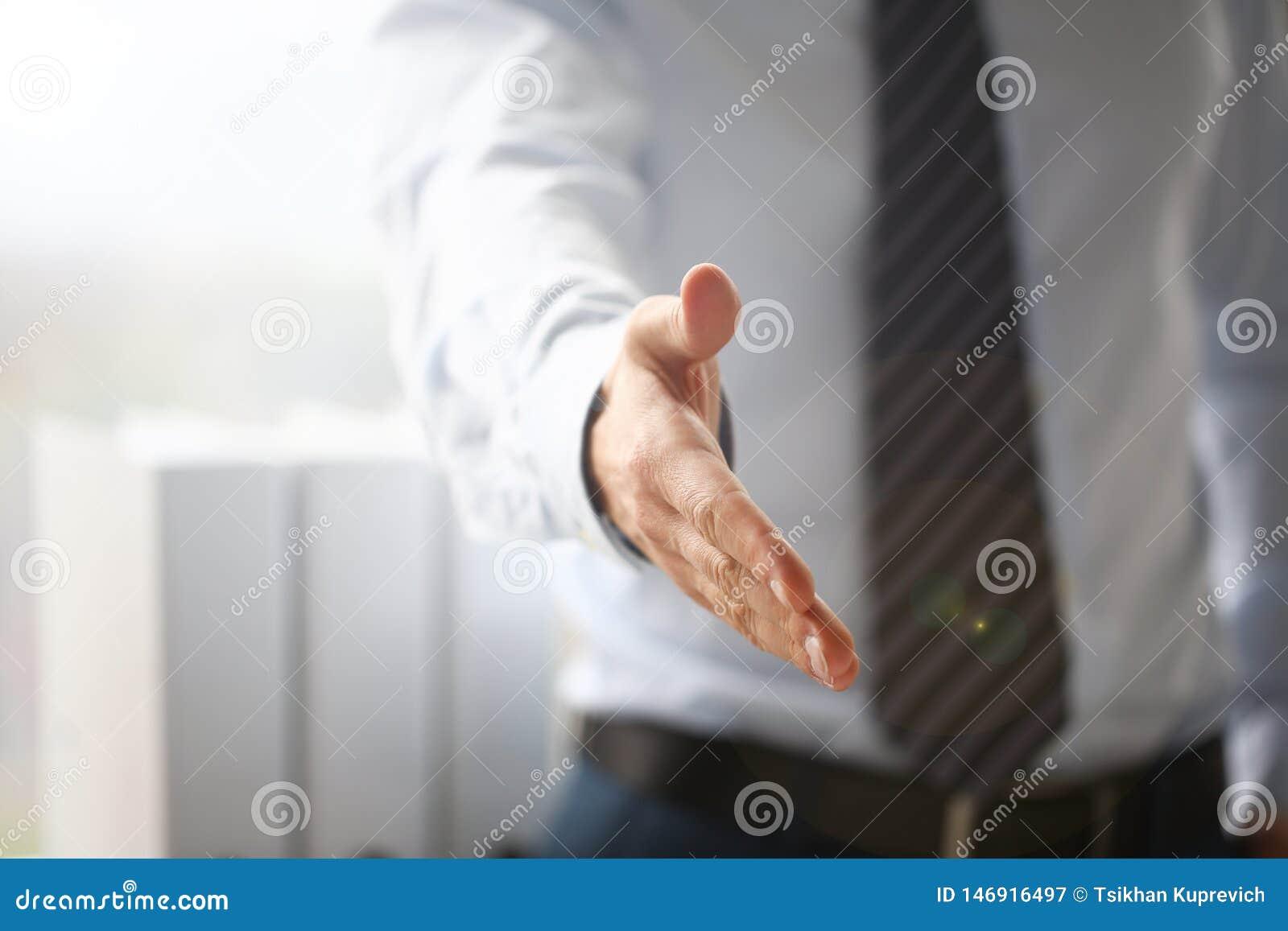 El hombre en traje y el lazo dan la mano como hola en primer de la oficina