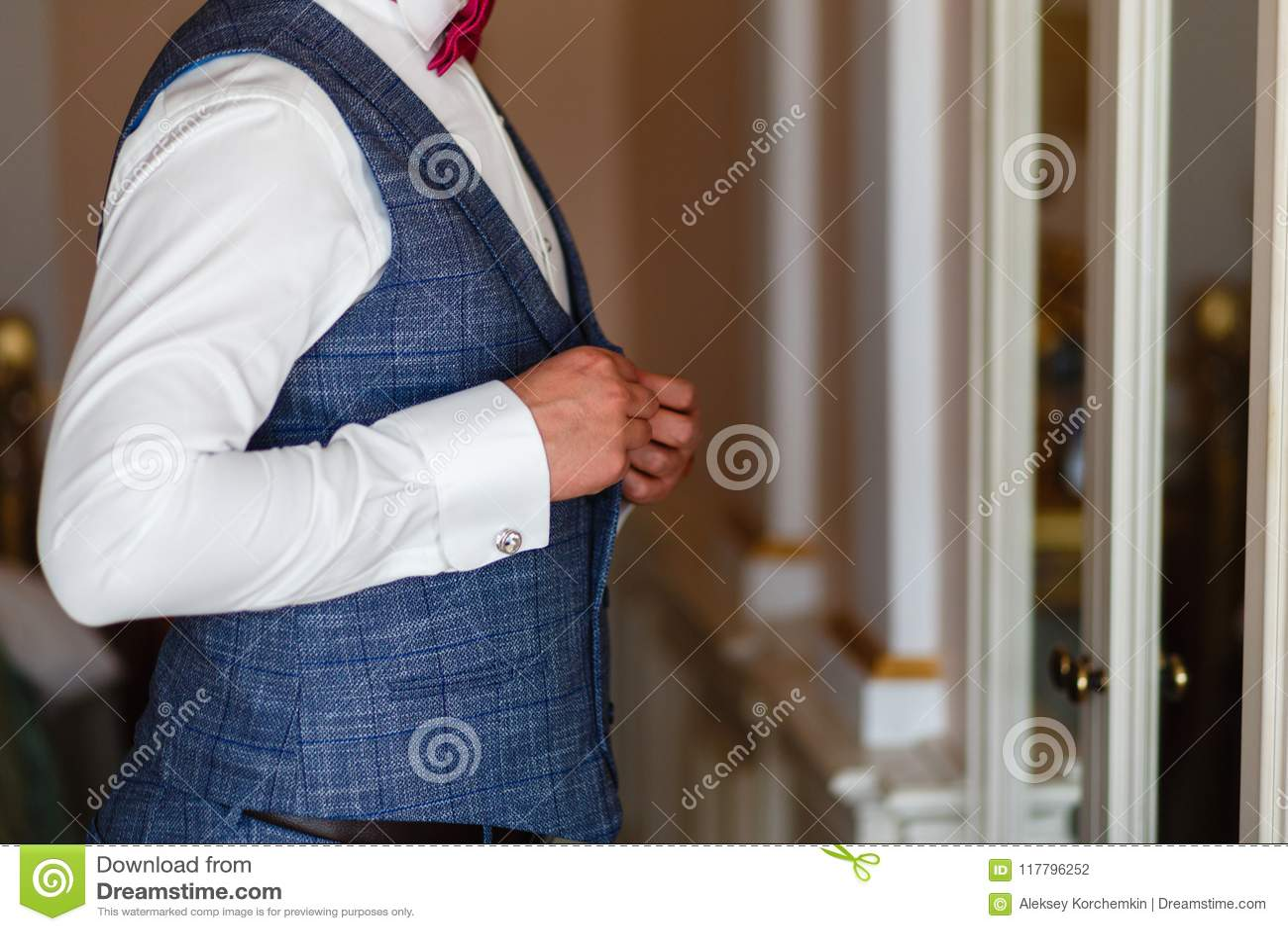 El hombre en una camisa blanca y un chaleco gris sujeta los botones delante del espejo Novio en traje gris y lazo que consigue li