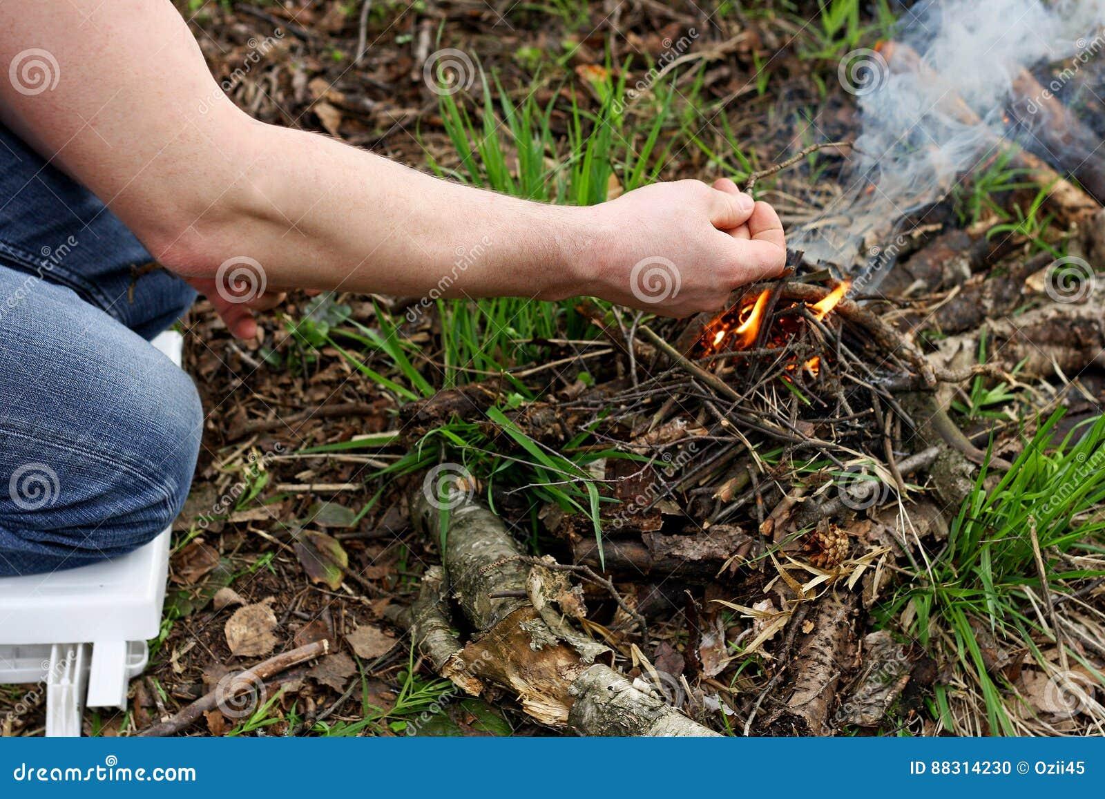 El hombre enciende un fuego en el bosque