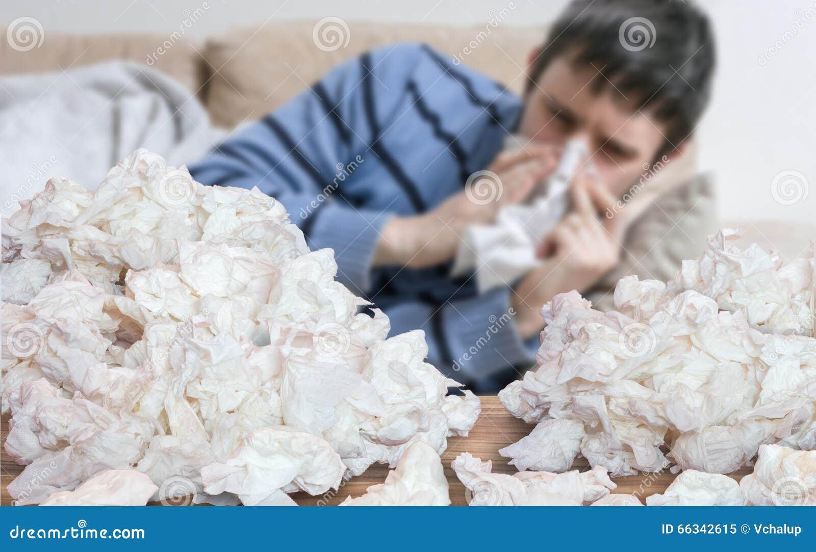 El hombre enfermo divertido que tiene gripe o frío está soplando su nariz