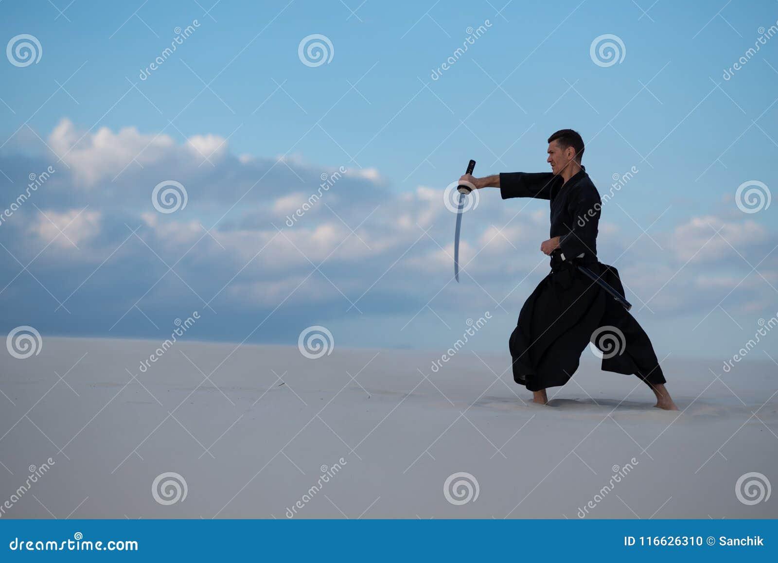 El hombre enfocado, en ropa japonesa tradicional, está practicando el centro comercial