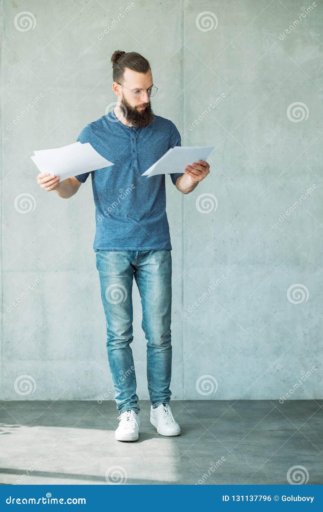 El hombre enfocado leyó la información de los documentos de negocio