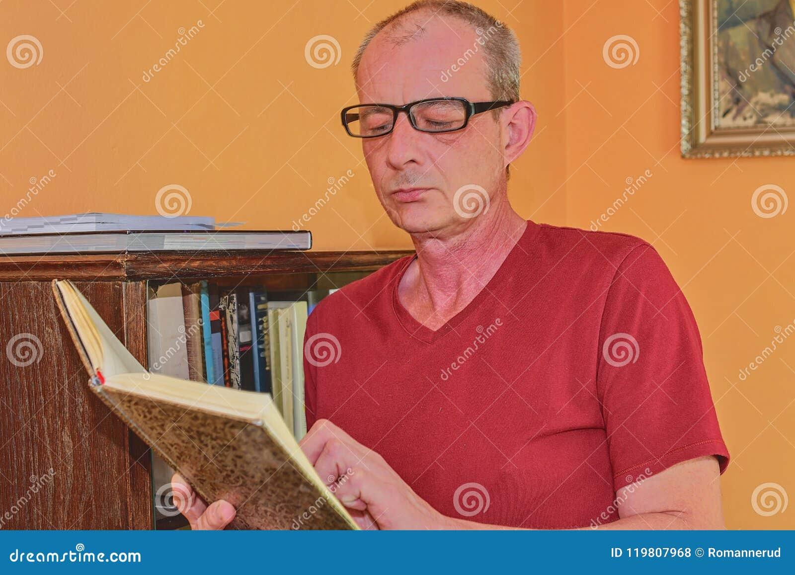 El hombre envejecido centro del hombre es libro de lectura en sala de estar El hombre maduro se está colocando al lado del estant