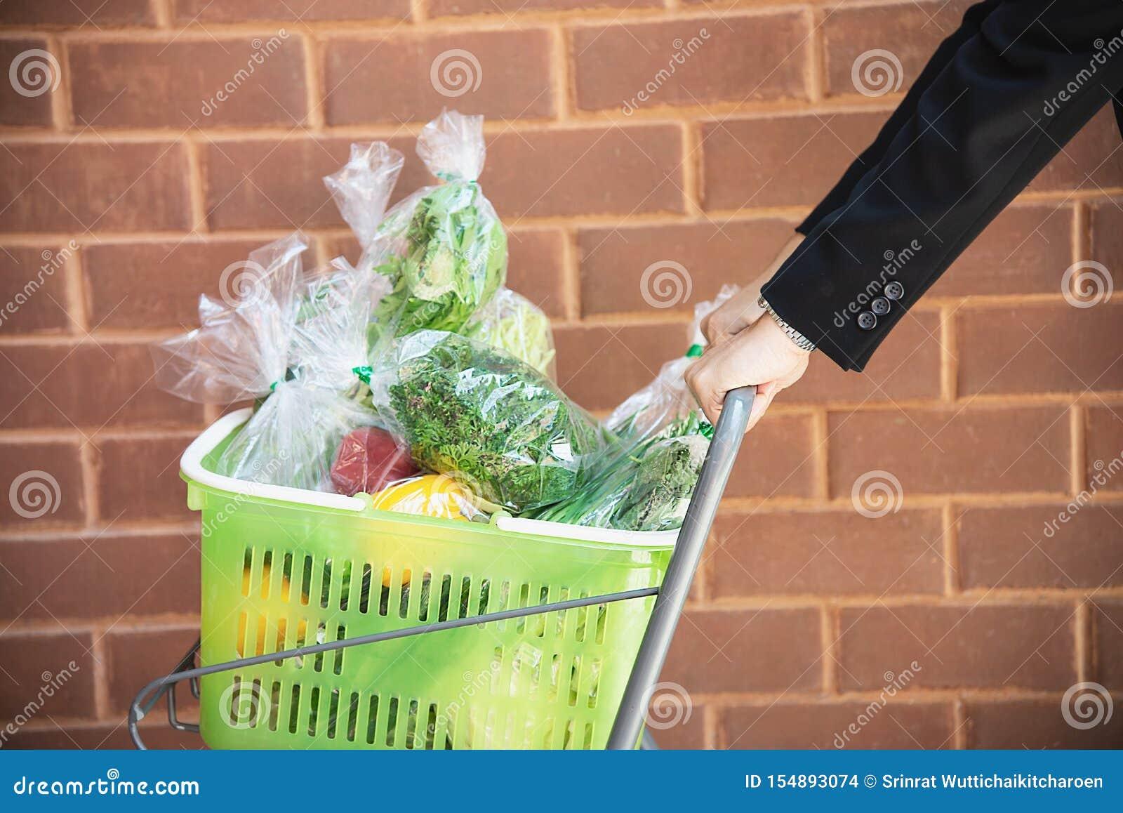 El hombre es verduras frescas que hacen compras en tienda del supermercado