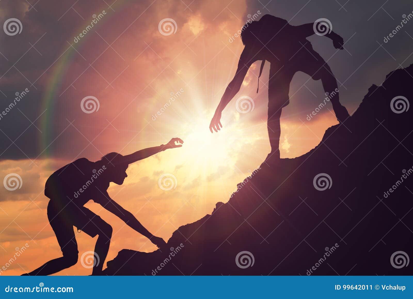 El hombre está dando la mano amiga Siluetas de la gente que sube en la montaña en la puesta del sol